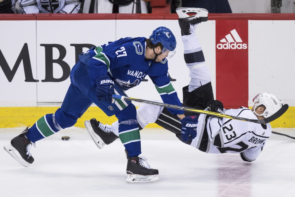 Vancouver Canucks' Ben Hutton, left, checks Los Angeles Kings' Dustin Brown during the second period of an NHL hockey game Saturday, Dec. 30, 2017, in...