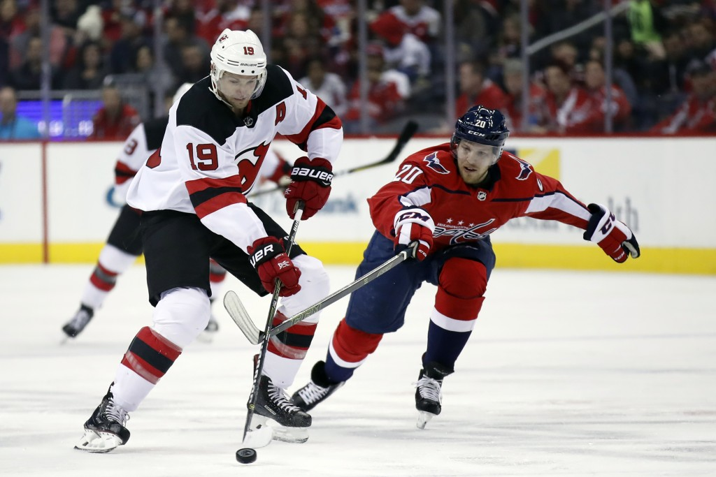 New Jersey Devils center Travis Zajac (19) skates with the puck as Washington Capitals center Lars Eller (20), from Denmark, pressures in the first pe...