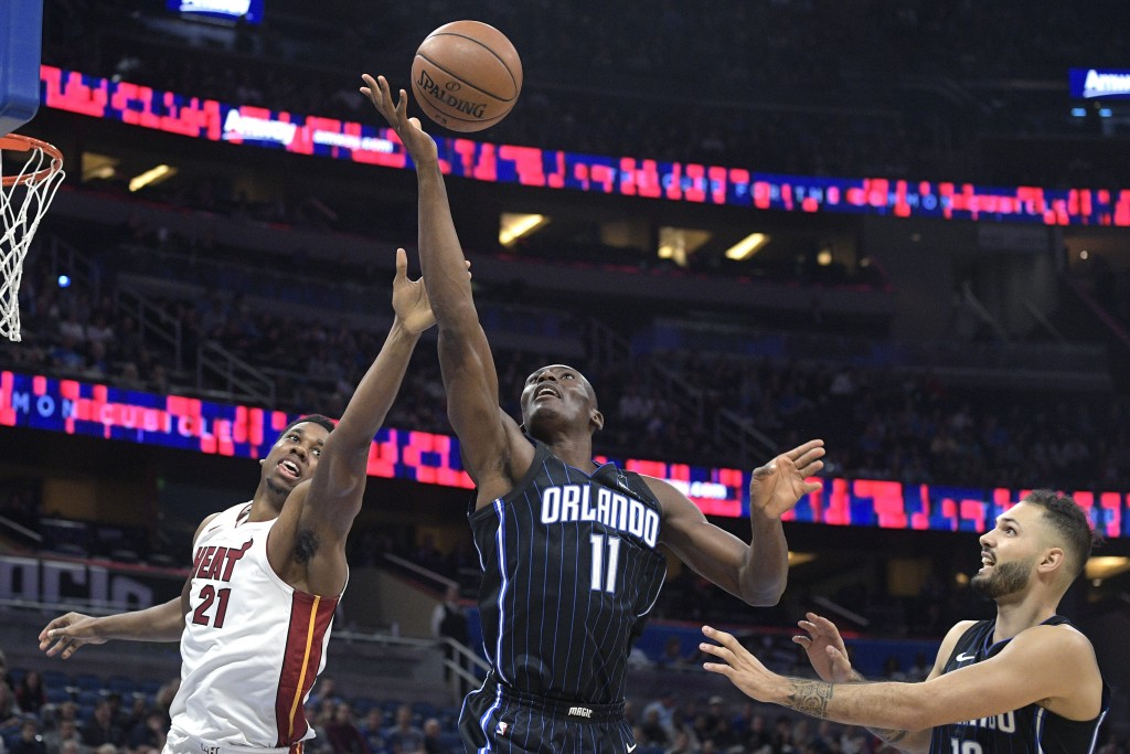 Miami Heat center Hassan Whiteside (21) and Orlando Magic center Bismack Biyombo (11) fight for a rebound as Magic forward Evan Fournier, right, watch...