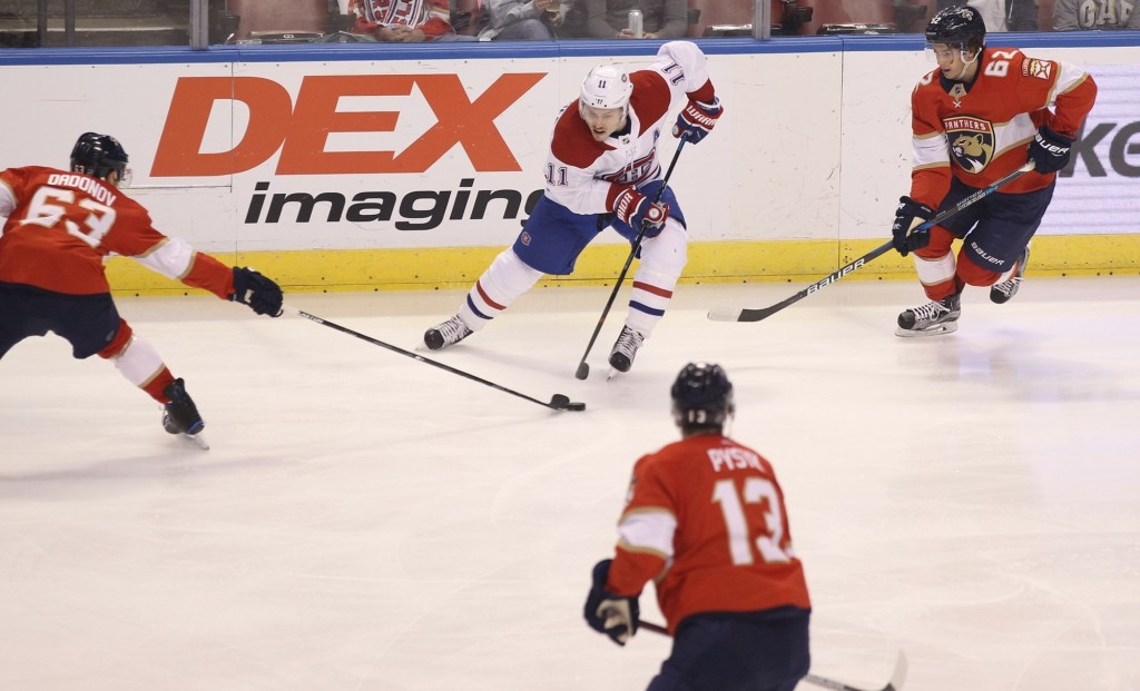 Montreal Canadiens' Brendan Gallagher (11) moves the puck against Florida Panthers' Evgenii Dadonov (63), of Russia, Mark Pysyk (13) and Denis Malgin,...