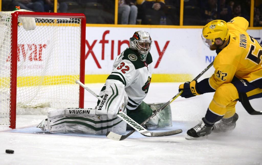 Minnesota Wild goalie Alex Stalock (32) stops a shot by Nashville Predators defenseman Matt Irwin (52) in the second period of an NHL hockey game Satu...
