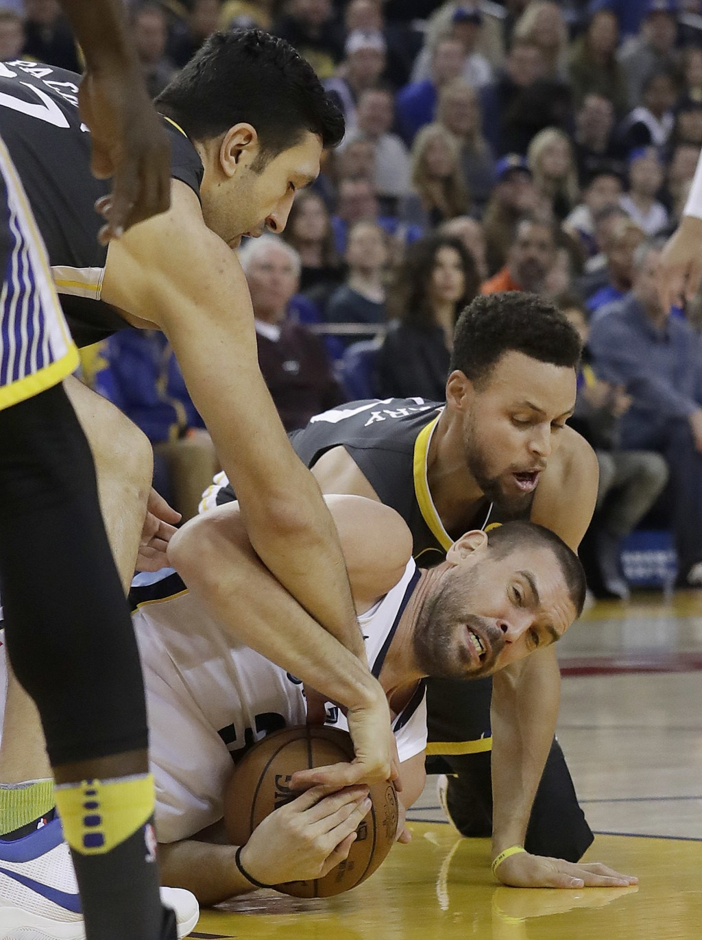 Memphis Grizzlies center Marc Gasol, bottom, tries to hold on to the ball under Golden State Warriors center Zaza Pachulia, left, and guard Stephen Cu...
