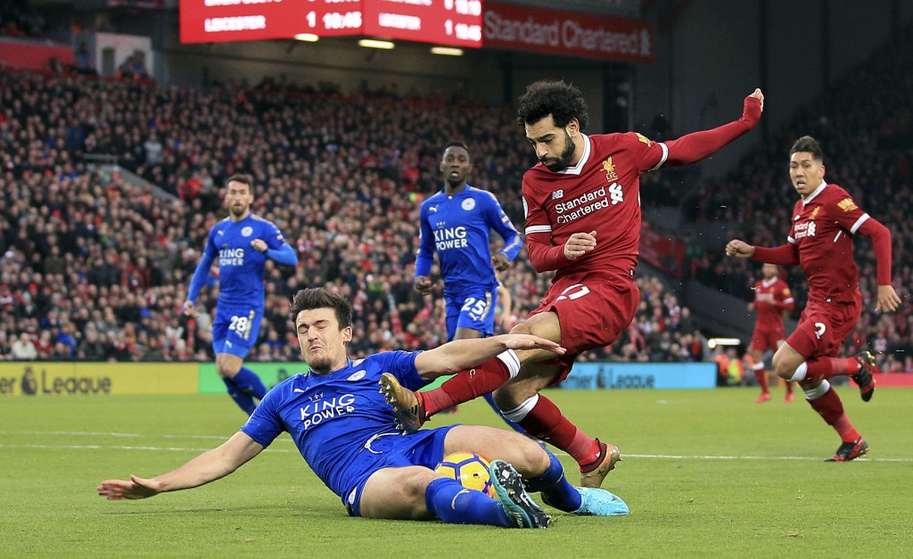 Leicester City's Harry Maguire, left, and Liverpool's Mohamed Salah battle for the ball during the English Premier League soccer match at Anfield, Liv...