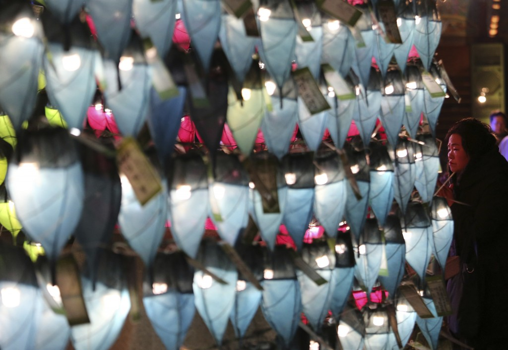 A woman prays in front of lanterns to celebrate the New Year at Jogyesa Buddhist temple in Seoul, South Korea, Sunday, Dec. 31, 2017. (AP Photo/Ahn Yo...