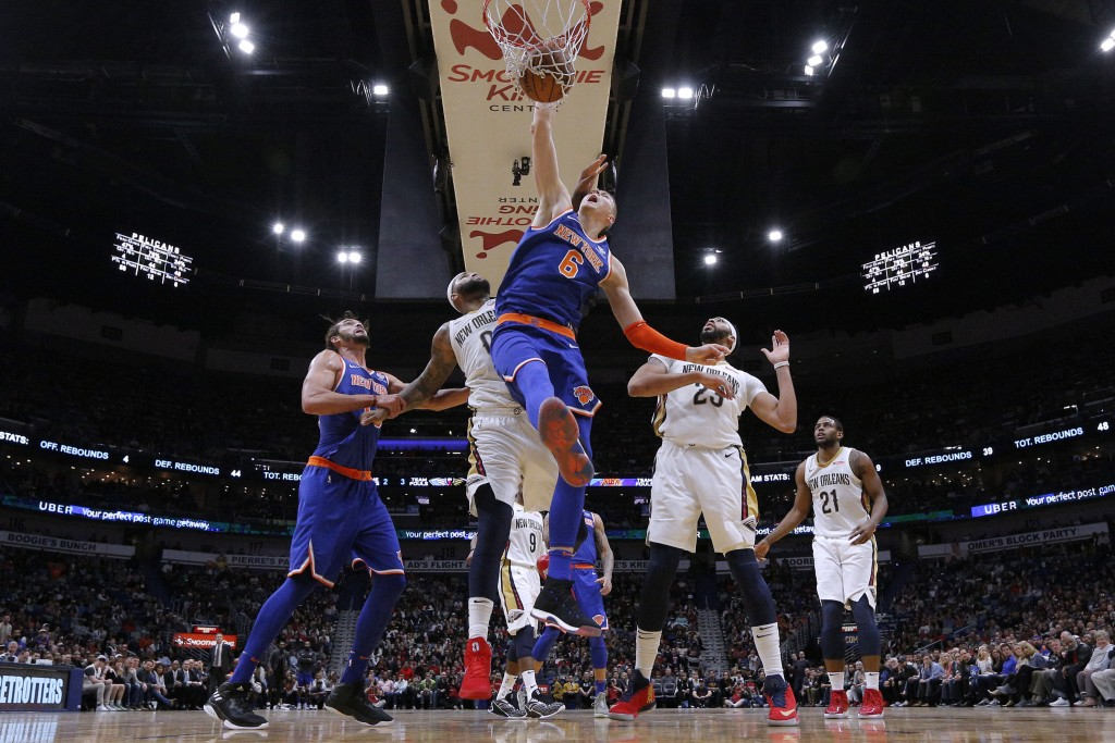 New York Knicks forward Kristaps Porzingis (6) dunks over New Orleans Pelicans forward Anthony Davis (23) and center DeMarcus Cousins (0) during the s...