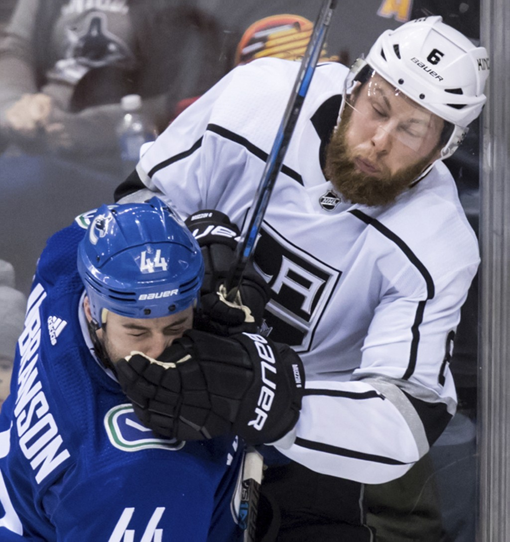 Vancouver Canucks' Erik Gudbranson, left, and Los Angeles Kings' Jake Muzzin collide during the third period of an NHL hockey game Saturday, Dec. 30, ...