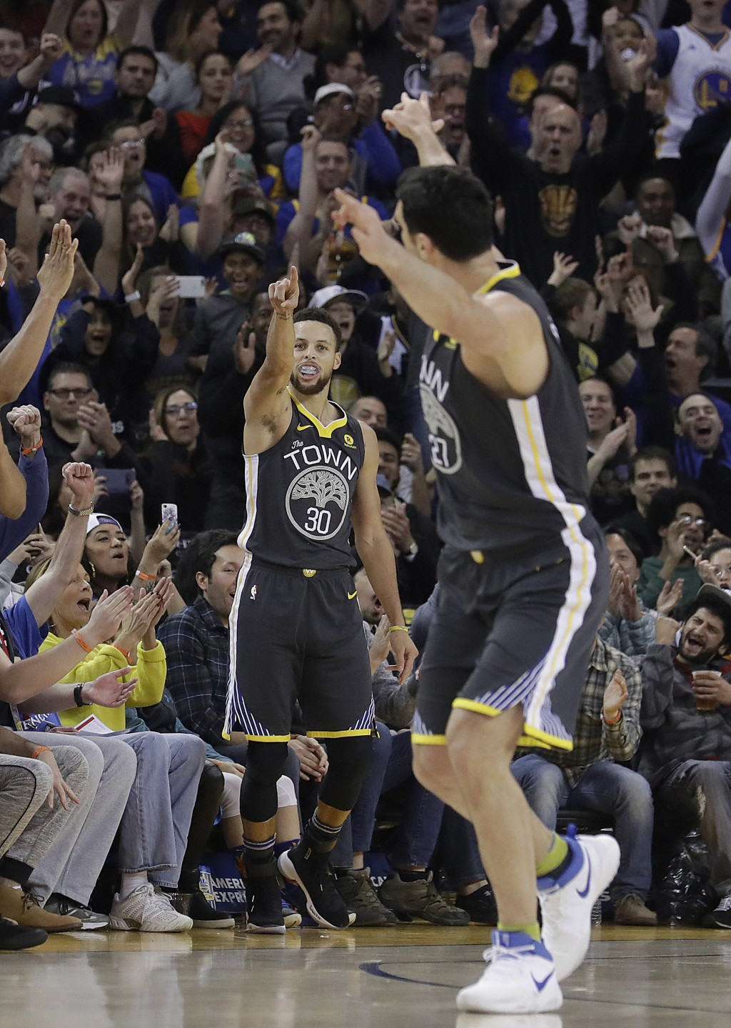 Golden State Warriors guard Stephen Curry (30) points toward center Zaza Pachulia after Curry scored during the first half of an NBA basketball game a...