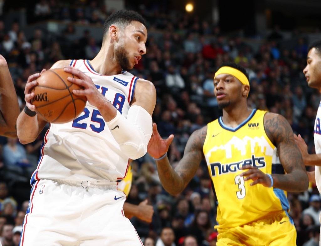 Philadelphia 76ers guard Ben Simmons, left, pulls in a rebound in front of Denver Nuggets guard Torrey Craig in the first half of an NBA basketball ga...