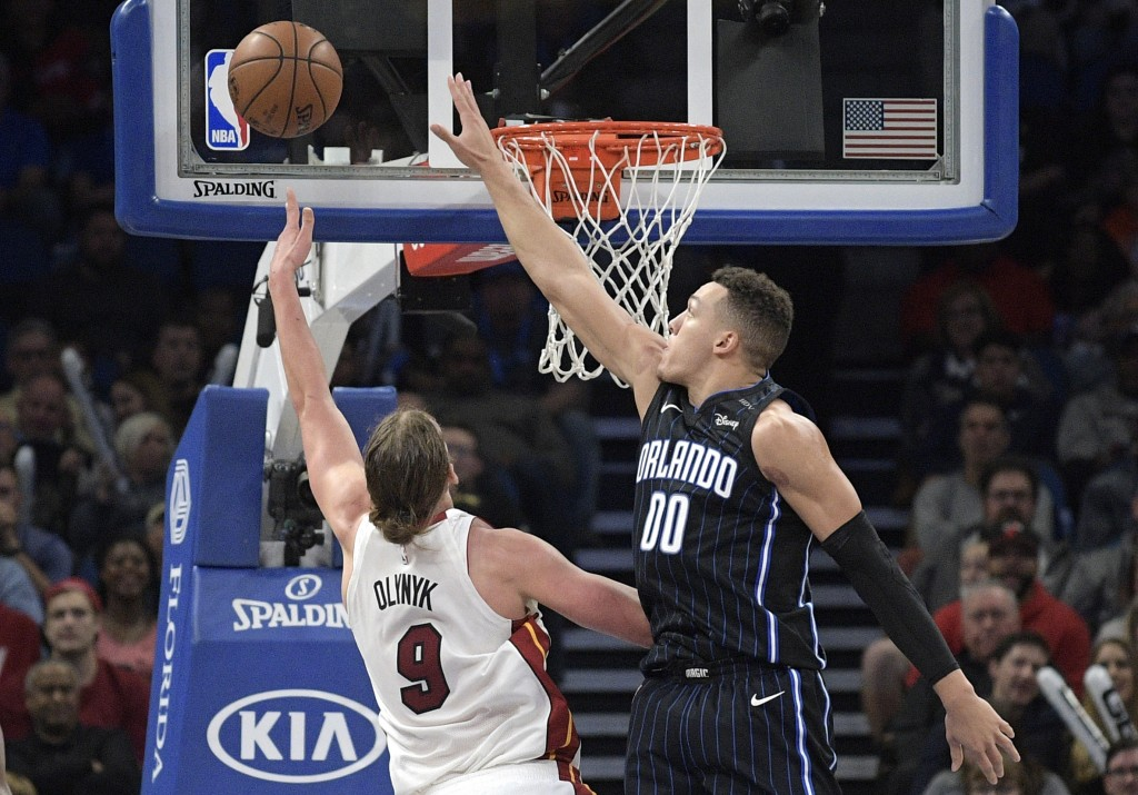 Miami Heat center Kelly Olynyk (9) goes up for a shot in front of Orlando Magic forward Aaron Gordon (00) during the first half of an NBA basketball g...