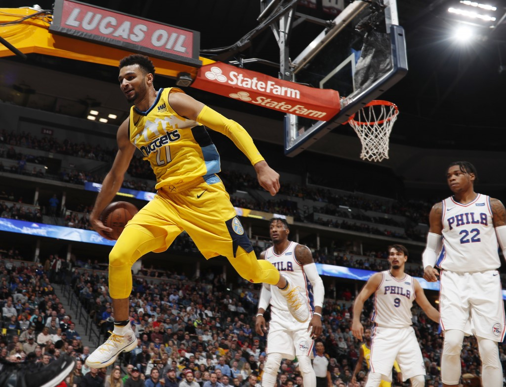 Denver Nuggets guard Jamal Murray, left, flies out of bounds while trying to save a loose ball as, from back left, Philadelphia 76ers forwards Robert ...