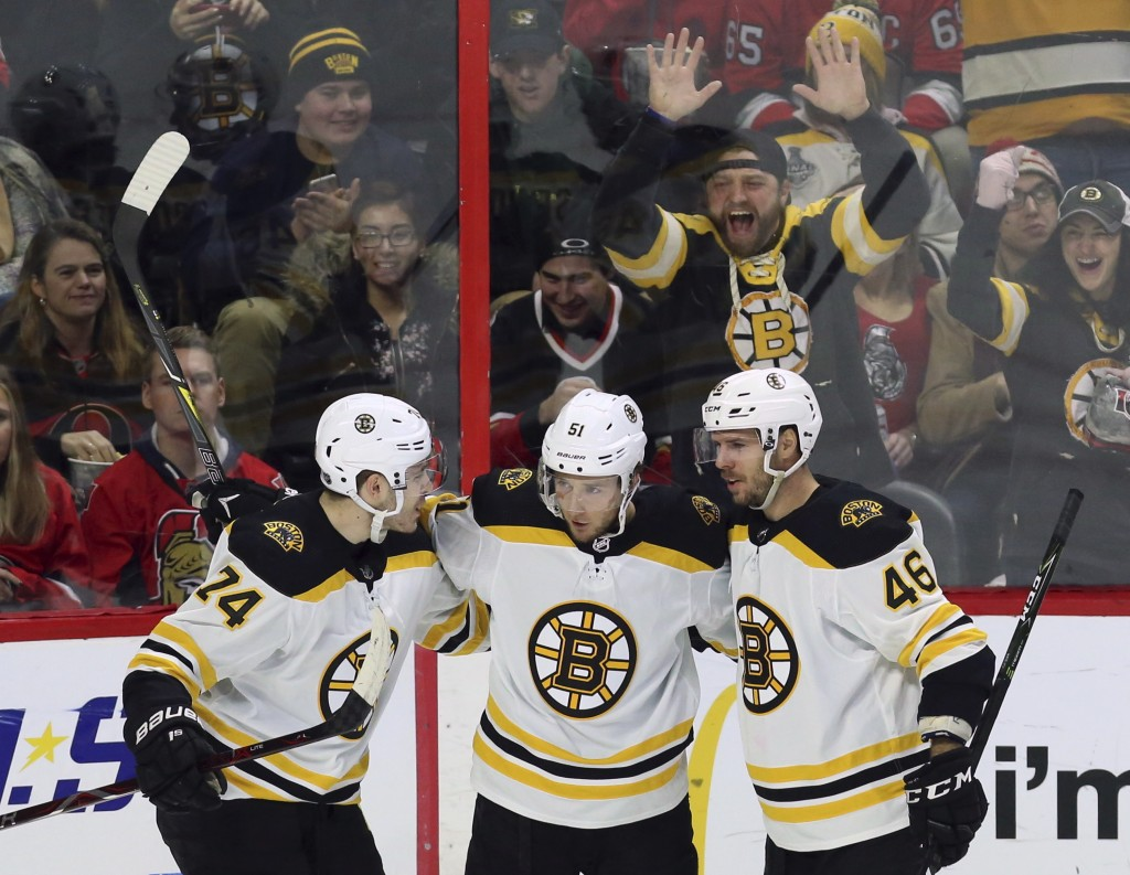 Boston Bruins' Ryan Spooner (51) celebrates his second goal of the night with teammates David Krejci (46) and Jake DeBrusk (74), against the Ottawa Se...