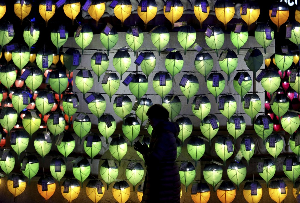 In this Dec. 31, 2017, file photo, a woman prays in front of lanterns to celebrate the New Year at Jogyesa Buddhist temple in Seoul, South Korea. (AP ...