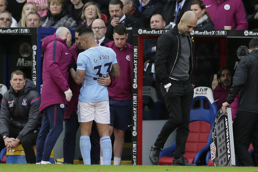 Manchester City manager Pep Guardiola, right, looks dejected as Manchester City's Gabriel Jesus is taken off the pitch injured during the English Prem...