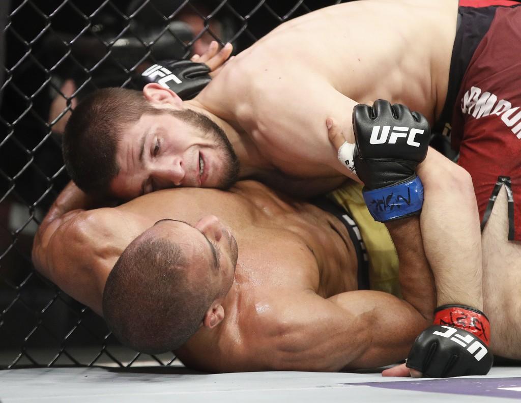 Khabib Nurmagomedov, top, fights Edson Barboza in a lightweight mixed martial arts bout at UFC 219, Saturday, Dec. 30, 2017, in Las Vegas. (AP Photo/J...