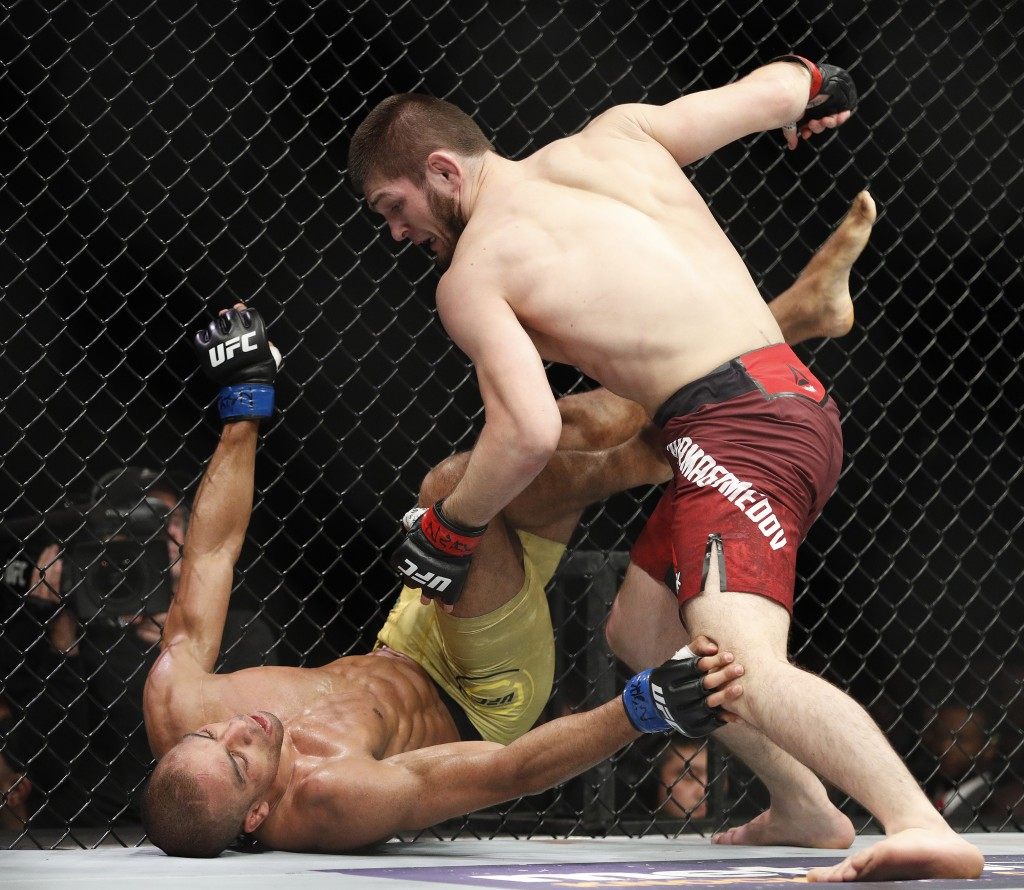 Khabib Nurmagomedov, right, fights Edson Barboza during a lightweight mixed martial arts bout at UFC 219, Saturday, Dec. 30, 2017, in Las Vegas. (AP P...