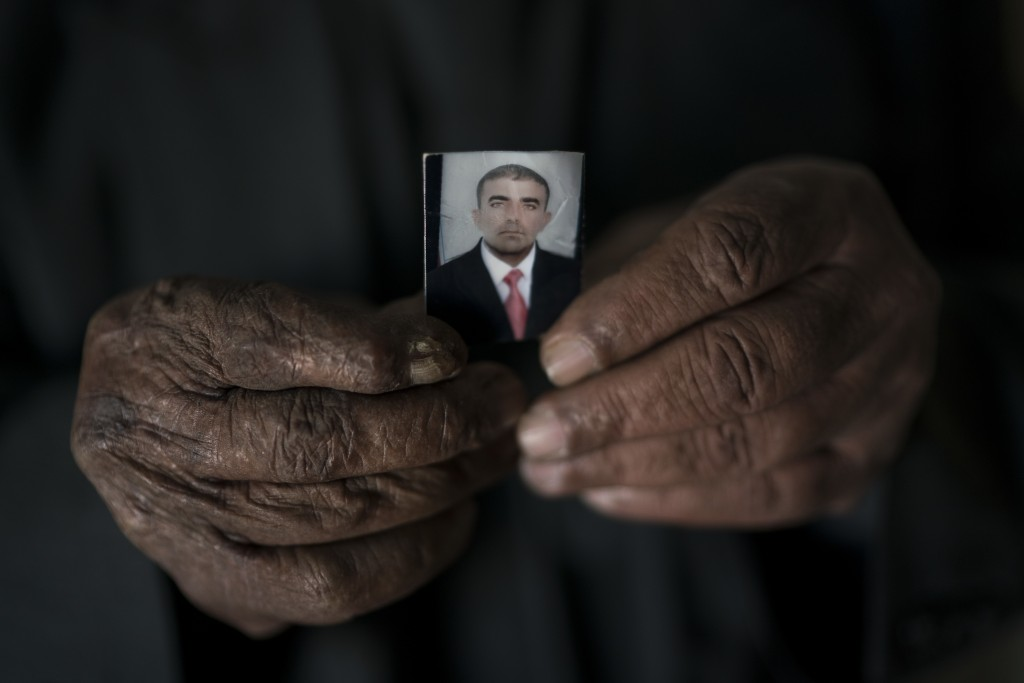 In this Nov. 12, 2017 photo, Ghanim Ahmed holds the photo of his son Ghazwan Ahmed, who was taken by unidentified gunmen after their village was liber...