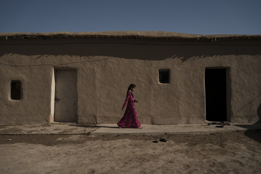 In this Nov. 12, 2017 photo, a girl walks outside her home in the Bijwaniya village, south of Mosul, Iraq. Five young men were taken by unidentified g...