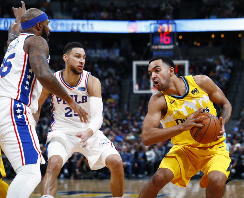 Denver Nuggets forward Trey Lyles, right, looks to shoot the ball as Philadelphia 76ers forward Trevor Booker, left, and guard Ben Simmons defend in t...