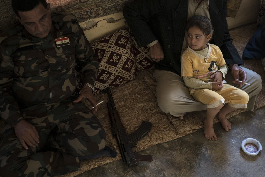 In this Nov. 12, 2017 photo, a local fighter and residents gather at the mayor's home in the Bijwaniya village, south of Mosul, Iraq. Five young men w...