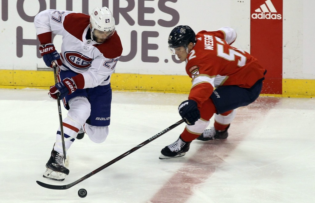 Montreal Canadiens' Alex Galchenyuk (27) moves the puck against Florida Panthers' MacKenzie Weegar, right, during the first period of an NHL hockey ga...