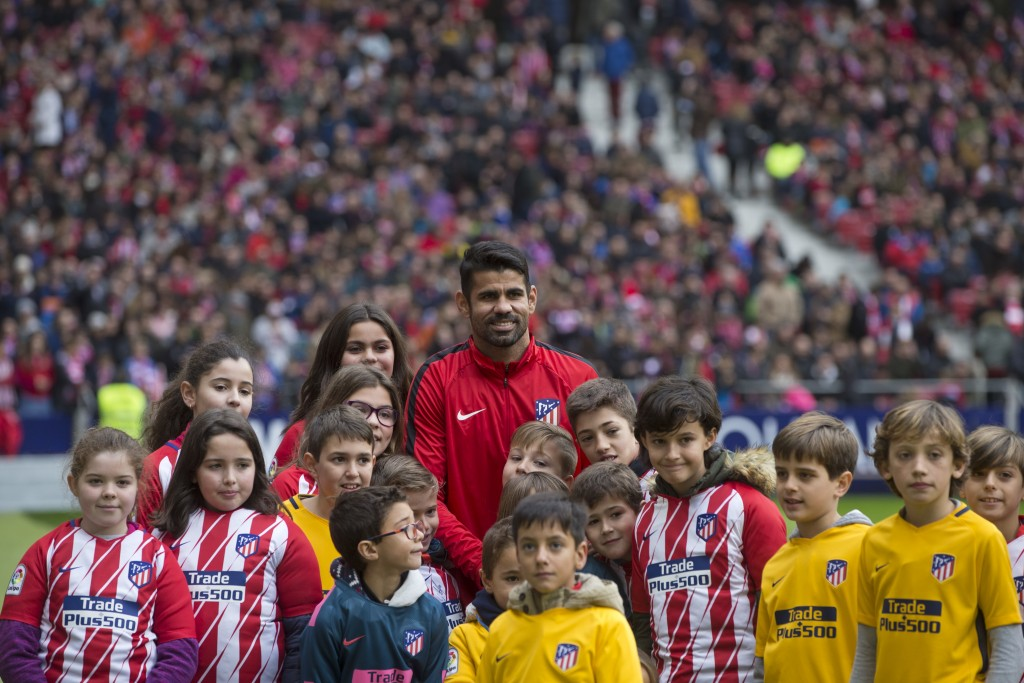 Diego Costa poses with children wearing Atletico shirts during his official presentation for Atletico Madrid at the Wanda Metropolitano stadium in Mad...