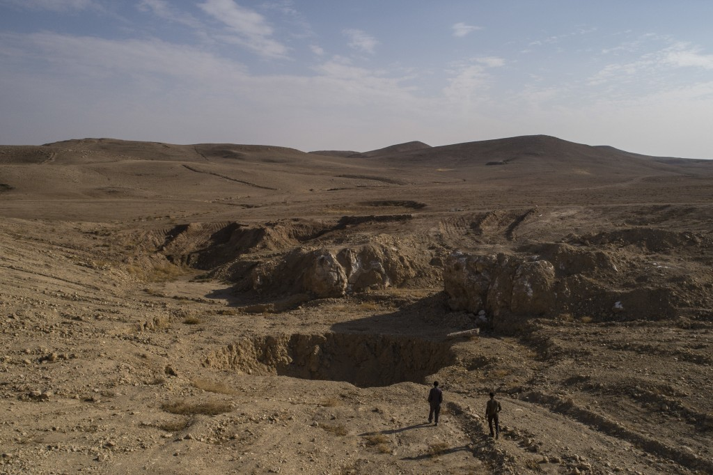 In this Nov. 11, 2017 photo, two Iraqi men walk near a sinkhole known as Khasfa, that is believed to contain the remains of people executed by Islamic...