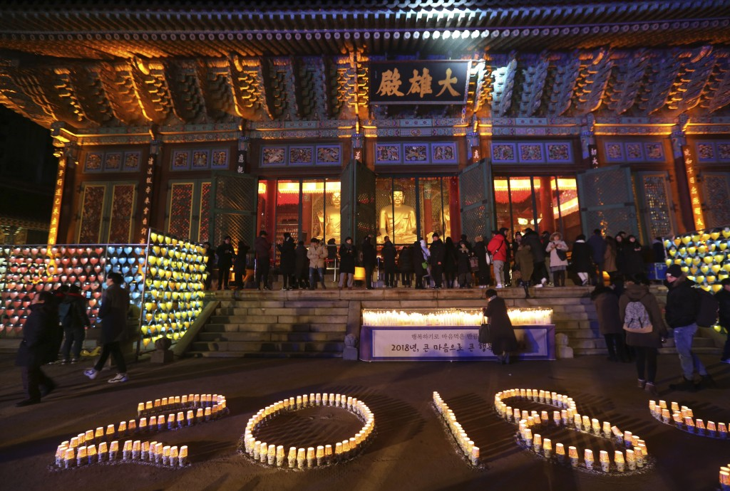 Buddhists light candles during New Year celebrations at Jogyesa Buddhist temple in Seoul, South Korea, Monday, Jan. 1, 2018. (AP Photo/Ahn Young-joon)