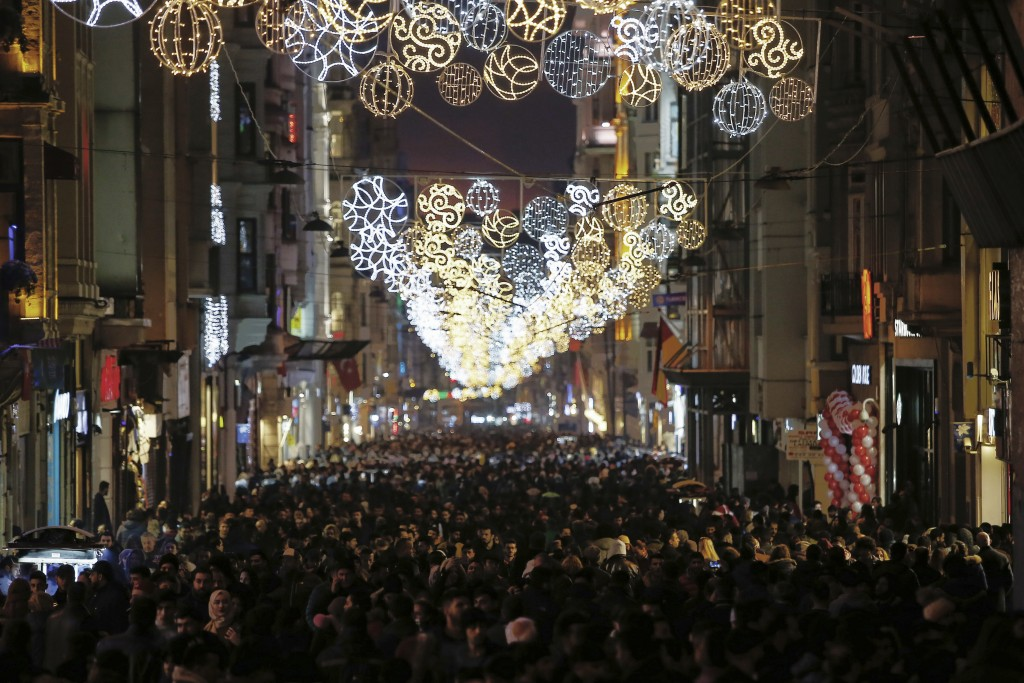 People walk in popular Istiklal Street near the city's main Taksim Square as people remember the victims of a deadly New Year's attack a year ago, in