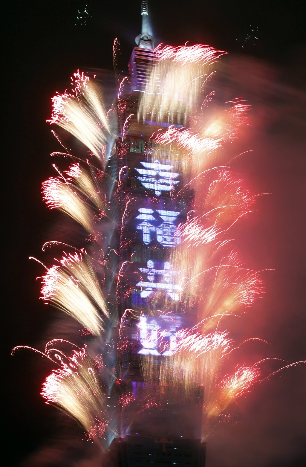"Fireworks explode with slogan reading ""Happiness and Good Condition Together"" on the Taipei 101 building during the New Year's celebrations in Taipei,"