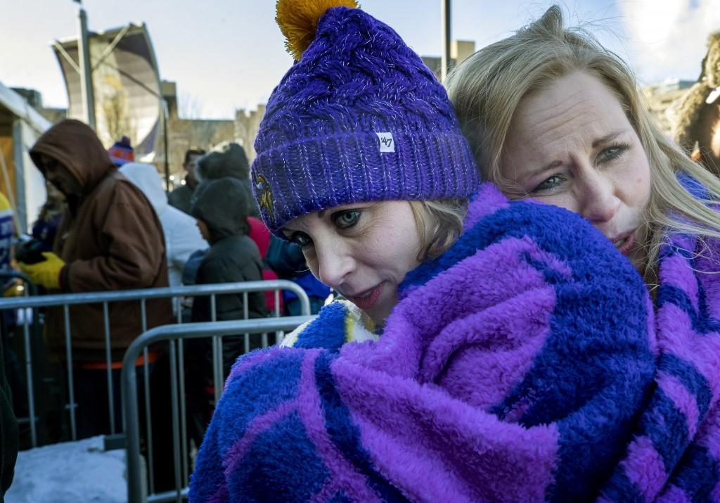 April Nickila and Christina Liesmaki try to stay warm while waiting in subzero temperatures to enter U.S. Bank Stadium to watch an NFL football game b