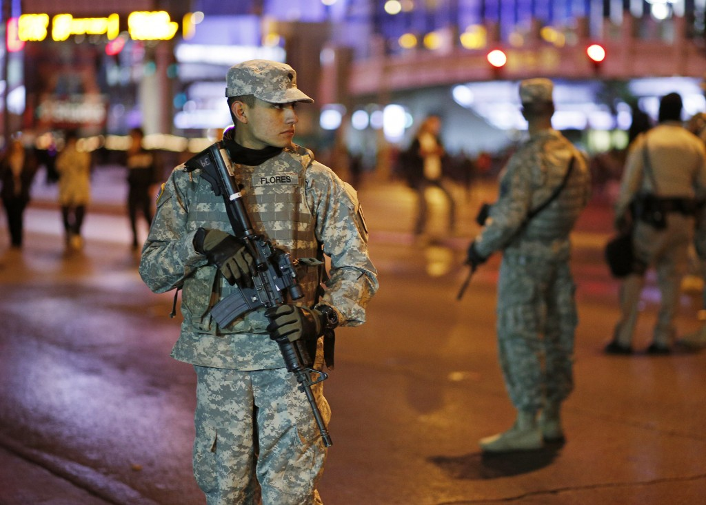 FILE - In this Dec. 31, 2015, file photo, members of the Nevada National Guard keep watch during New Year's Eve celebrations in Las Vegas. Tens of tho