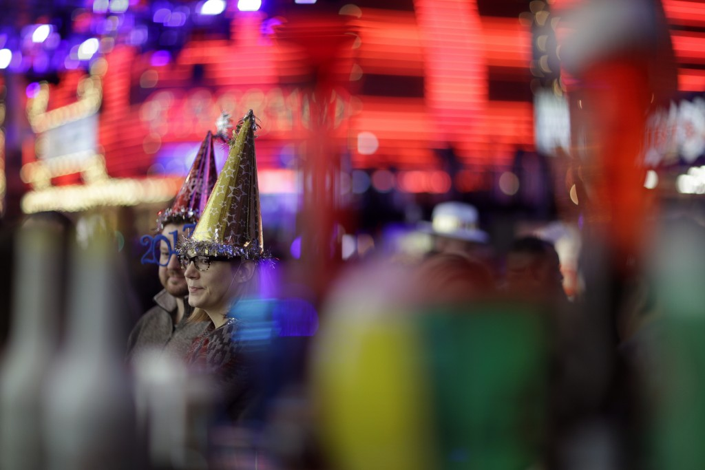 FILE - In this Dec. 31, 2016, file photo, People attend a New Year's Eve celebration in Las Vegas. Tens of thousands of revelers will ring in the New