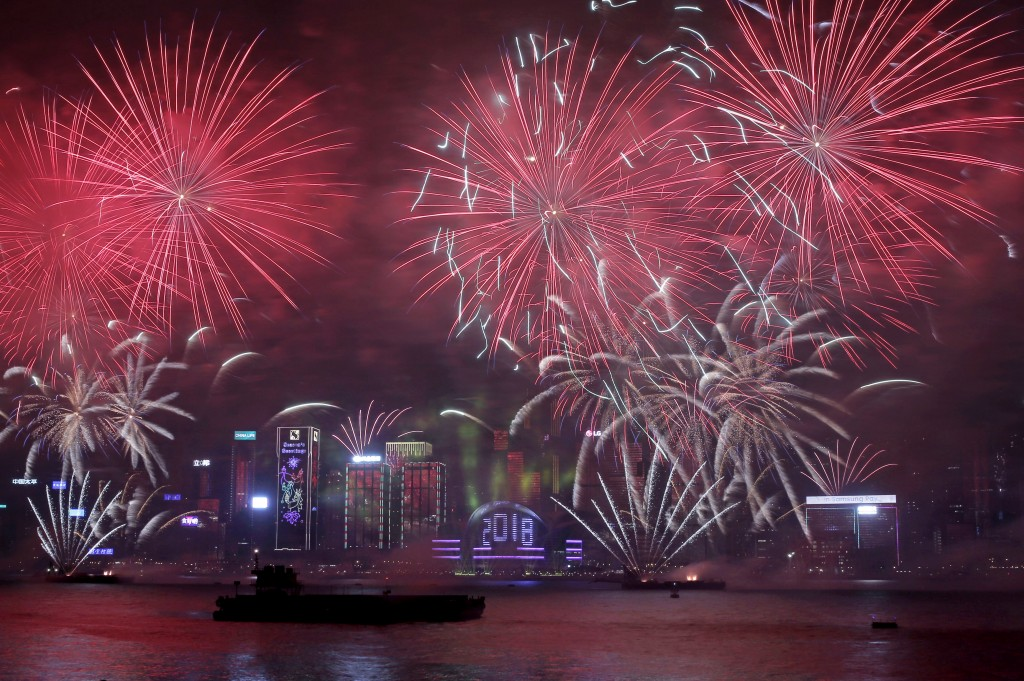 Fireworks explode over the Victoria Harbor during New Year's Eve to celebrate the start of year 2018 in Hong Kong, Monday, Jan. 1, 2018. (AP Photo/Kin