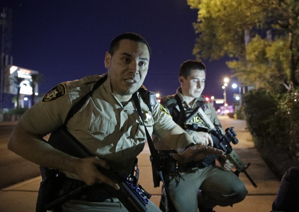 FILE - In this Oct. 1, 2017, file photo, police officers advise people to take cover near the scene of a shooting near the Mandalay Bay resort and cas