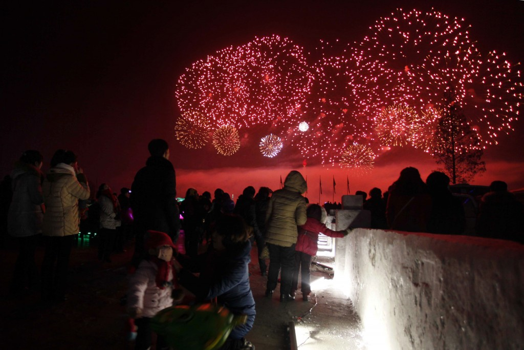 North Koreans watch as fireworks explode as part of New Year celebrations, above the Taedong River as viewed from Kim Il Sung Square, in Pyongyang, No