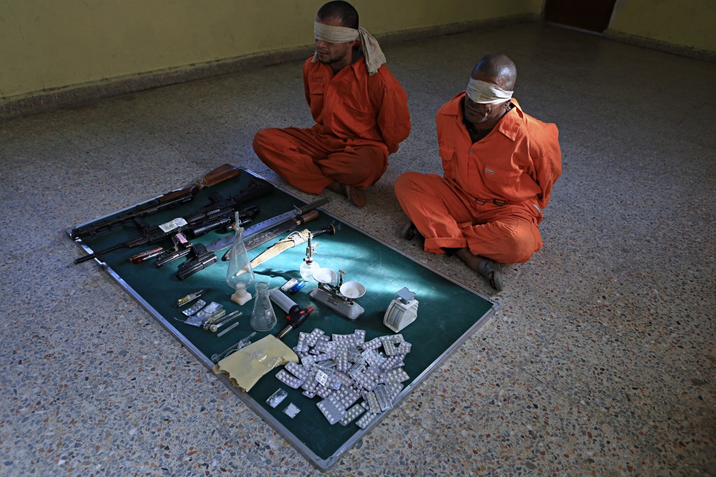 In this Tuesday, Dec. 5, 2017 photo, blindfolded suspected drug dealers are displayed with their goods and weapons in a detention facility in Basra, 3