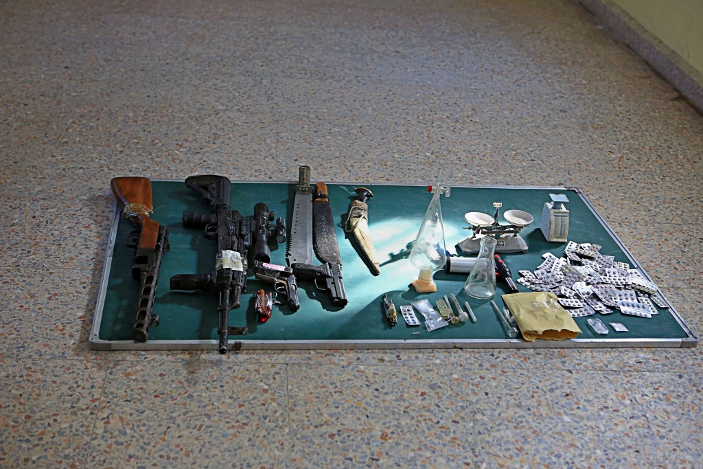 In this Tuesday, Dec. 5, 2017, drugs, manufacturing tools and weapons belonging to detained drug dealers are displayed in a detention facility in Basr
