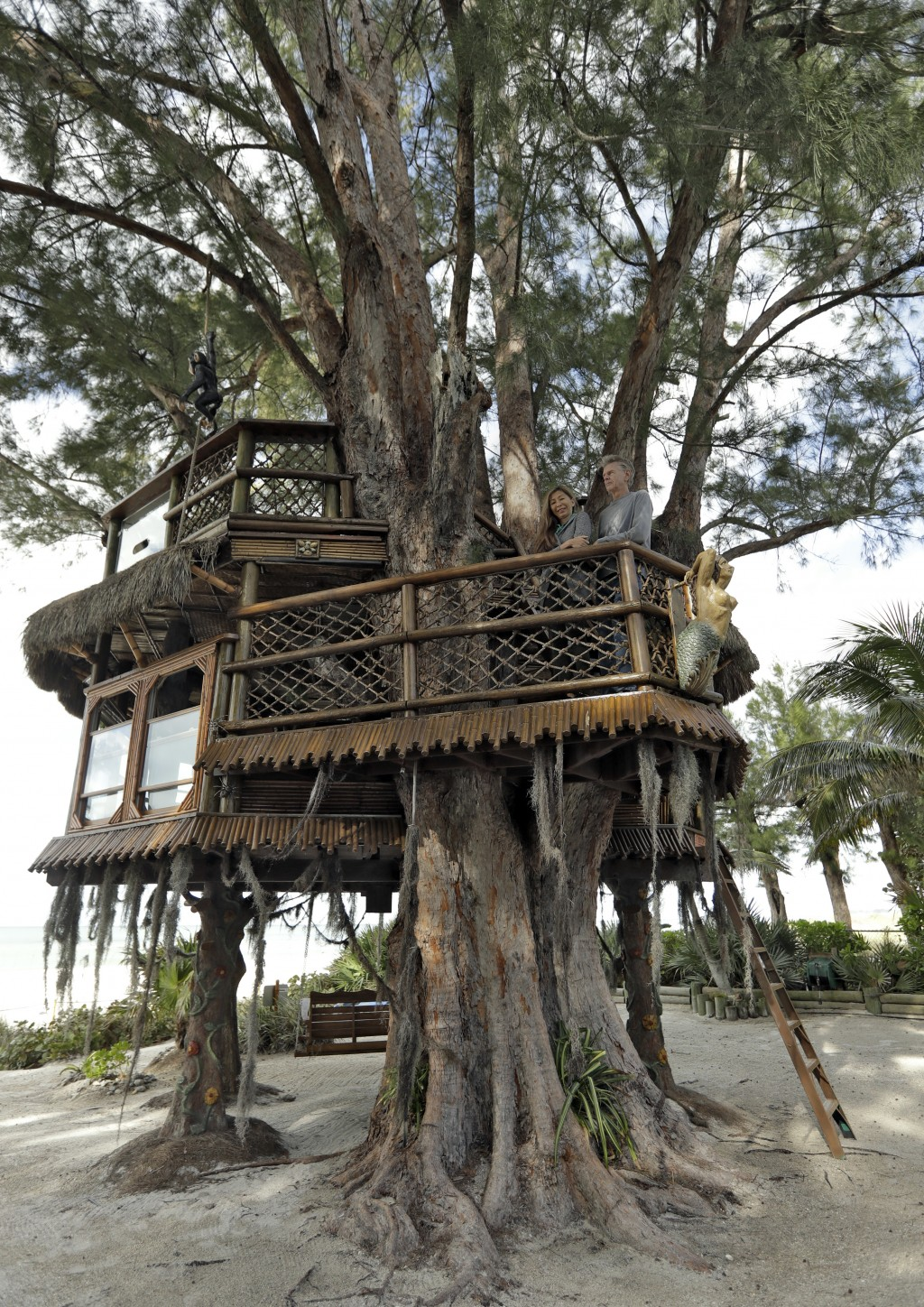 Lynn Tran and her husband Richard Hazen pose in their Australian pine treehouse Thursday, Jan. 4, 2018, in Holmes Beach, Fla. The couple is hoping the...