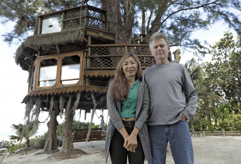 Lynn Tran and her husband Richard Hazen pose near their Australian pine treehouse Thursday, Jan. 4, 2018, in Holmes Beach, Fla. The couple is hoping t...