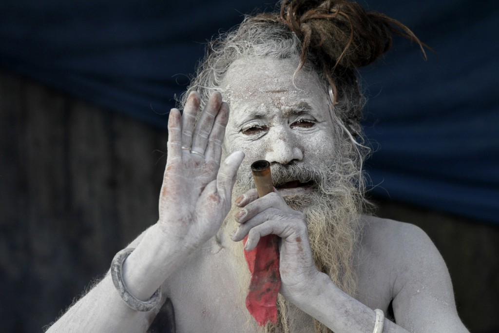 In this Sunday, Jan. 7, 2018, file photo, a sadhu, or a Hindu holy man, blesses a devotee as he smokes marijuana at a transit camp on the way to Ganga