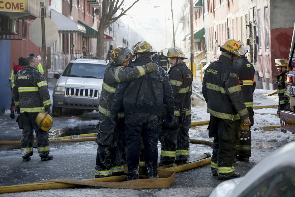 Firefighters embrace as their colleagues battle a row home fire in Philadelphia on Saturday, Jan. 6, 2018.  A veteran firefighter was fatally injured