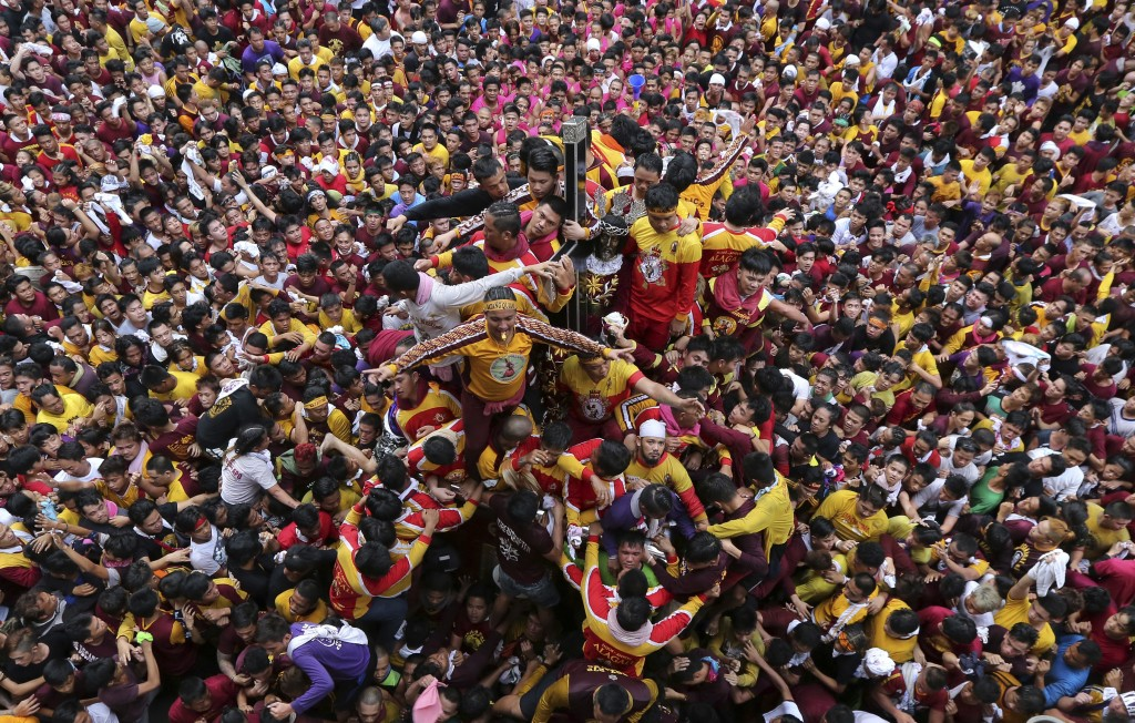 In this Tuesday, Jan. 9, 2018, file photo, Filipino Roman Catholic devotees jostle for position as they try to get near the image of the Black Nazaren