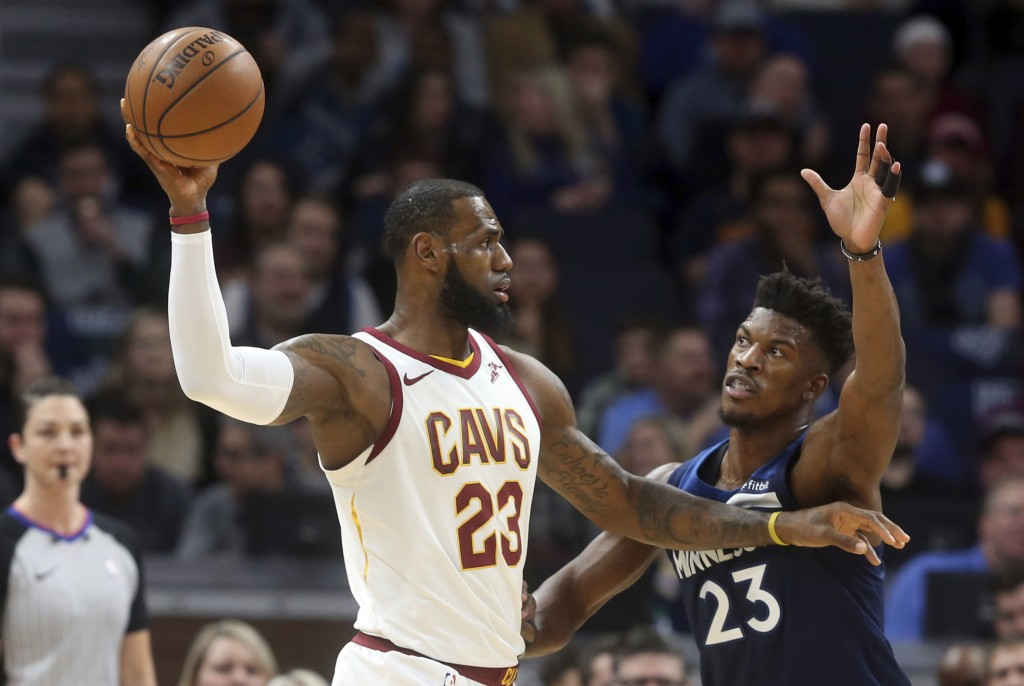 Cleveland Cavaliers' LeBron James,front left, looks to pass as Minnesota Timberwolves' Jimmy Butler defends in the first half of an NBA basketball gam
