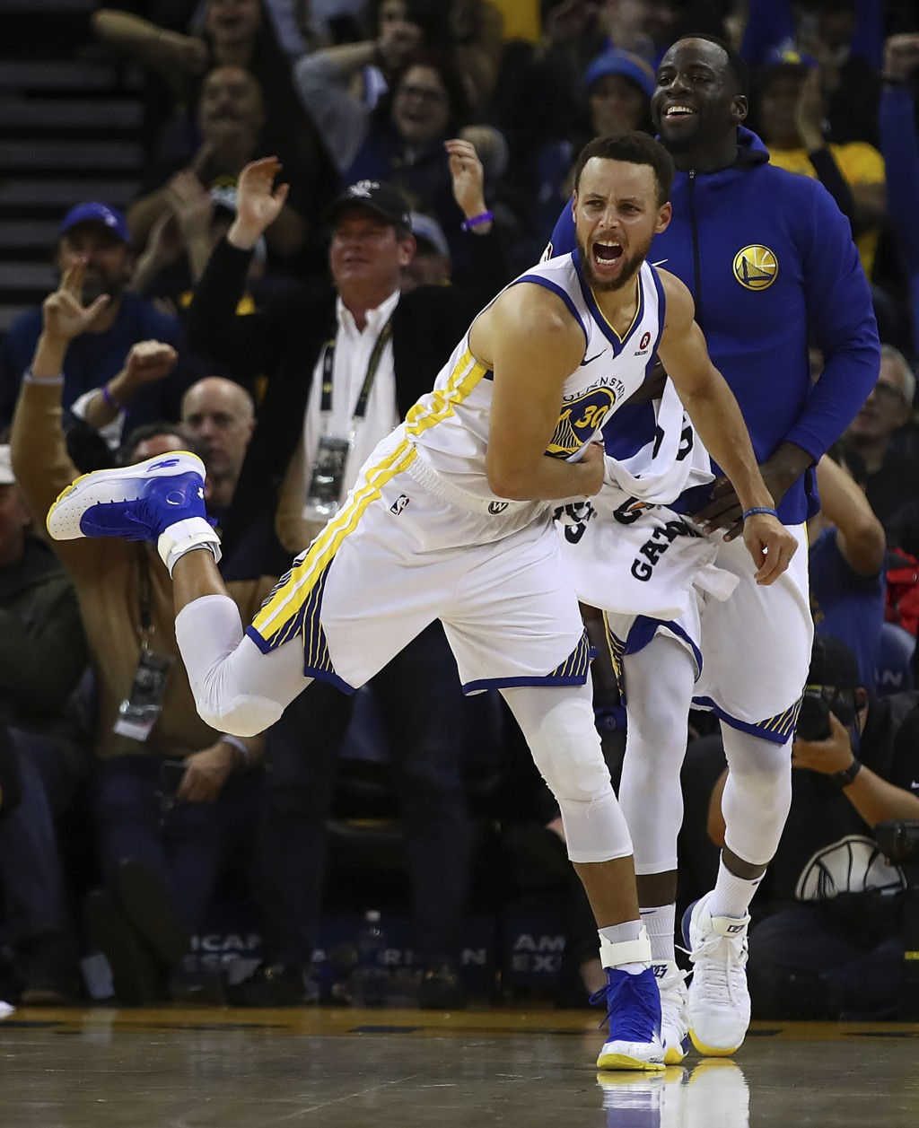 Golden State Warriors' Stephen Curry (30) and Draymond Green celebrate a score against the Denver Nuggets during the second half of an NBA basketball