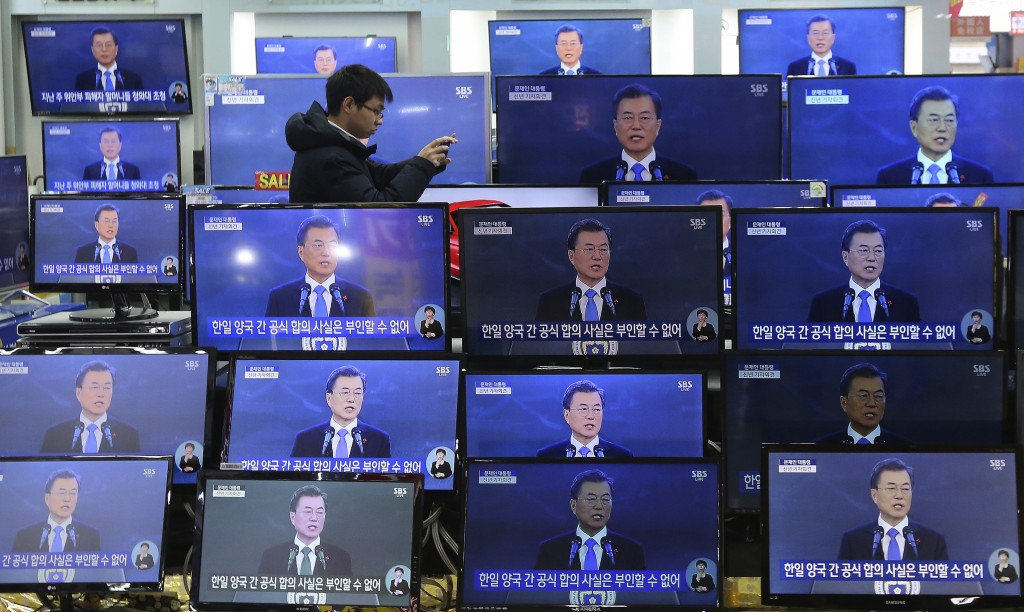In this Wednesday, Jan. 10, 2018, file photo, a man takes pictures next to TV screens showing the live broadcast of South Korean President Moon Jae-in