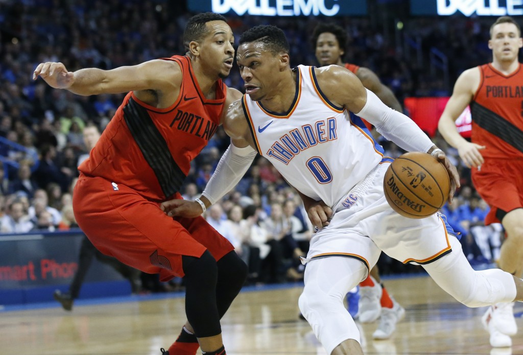 Oklahoma City Thunder guard Russell Westbrook (0) drives around Portland Trail Blazers guard C.J. McCollum during the first quarter of an NBA basketba