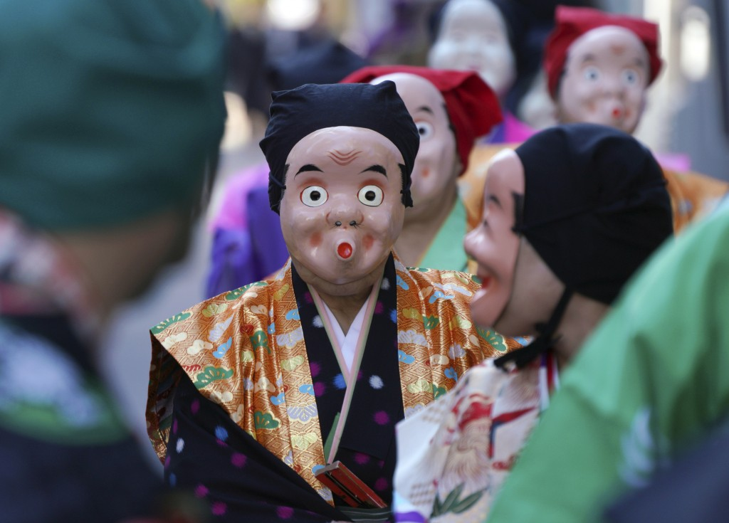 In this Wednesday, Jan. 10, 2018, file photo, artists wearing Japanese traditional clown masks march during the First Konpira Festival at Kotohiragu s