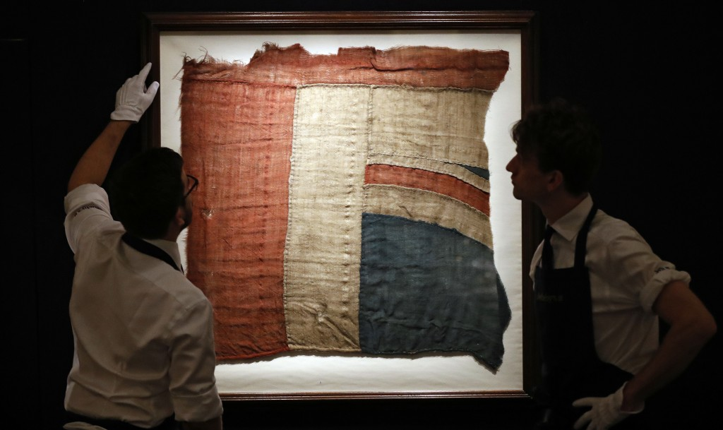 Sotheby's employees look at a frame with a fragment of a Union Jack in London, Thursday, Jan. 11, 2018. An exceptionally large fragment of the Union F