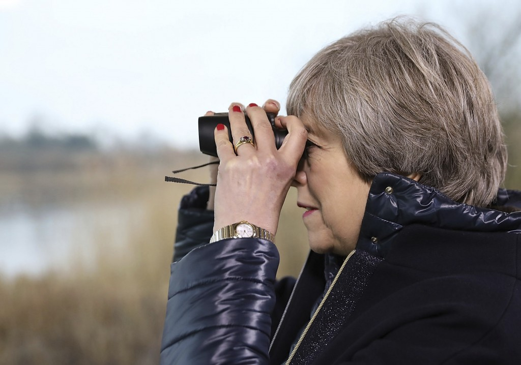 Britain's Prime Minister Theresa May looks through binoculars as she watches birds from inside a bird hide with school children at the London Wetland