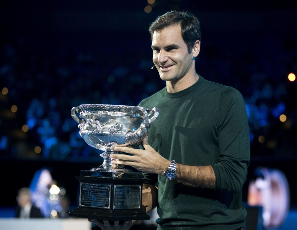 Defending men's singles champion Switzerland's Roger Federer poses for a photo with his trophy during a ceremony for the official draw at the Australi